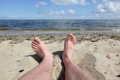 Man's legs on the beach - first person perspective Stock Photo