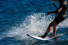 Man`s legs close up on a sailing Board surfing stock photo