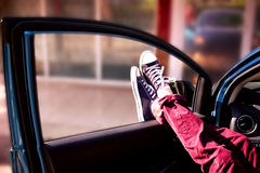 Man's legs in fashion burgundy pants and blue sneakers in the car Stock Photography