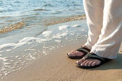 Man's  legs in an open shine on the sea shore Stock Photo