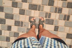 Man`s legs on paving tile from the first person top view. Summer look stock photo