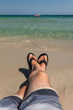 Man's Legs Relaxing at Beach. Men's legs relaxing at beach and extending to the water. Man is wearing shorts and fliip flops Stock Photo