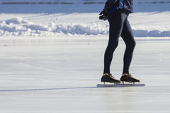 Man`s legs on skates ice ring - winter sport at sunny day Royalty Free Stock Photo
