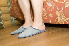 Man's legs in slippers Stock Photo