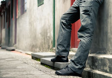 Man's legs standing against the wall stock photos