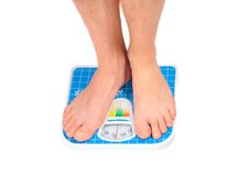 Man's legs ,weighed on floor scale. Royalty Free Stock Image