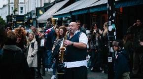 This man's music stops people who spend their time walking on the weekend market street, some of them dancing ,some of them w. Atching and laughing with Royalty Free Stock Images