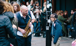 This man's music stops people who spend their time walking on the weekend market street, some of them dancing ,some of them w. Atching and laughing with Royalty Free Stock Photo