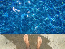 Man`s naked foot standing on edge of bright blue swimming pool. Man`s naked foot standing on edge of bright blue swimming pool, with water with sunlight Stock Photo