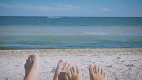 Man` s och fot för kvinna` s i sanden mot det skämtsamma havet och gyckel som vrida sig fingrar förbunden förälskelse roman stock video