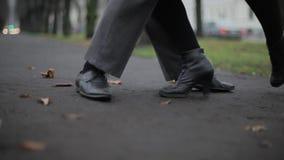 Man ` s, och foten för kvinna` s i svarta läderskor dansar på jordning som täckas av sidor