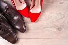 Man` s och röda kvinnors för hög häl skor på vit bakgrund Arkivfoton