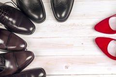 Man` s och röda kvinnors för hög häl skor på vit bakgrund Royaltyfri Fotografi