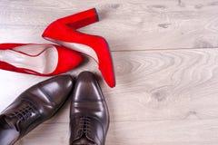 Man` s och röda kvinnors för hög häl skor på vit bakgrund Royaltyfria Bilder