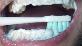 Man`s open mouth and brushes his teeth in morning. Close up white man brushing his teeth with toothbrush. Oral hygiene. Toothpaste in mouth and teeth stock footage