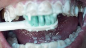 Man`s open mouth and brushes his teeth in morning. Close up white man brushing his teeth with toothbrush. Oral hygiene. Toothpaste in mouth and teeth stock video