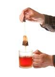Man?s passa la tazza di tè della holding e la bustina di tè Fotografie Stock
