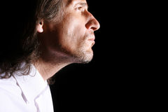 Man's portrait. On a black background.The man is photographed in a profile Stock Photo