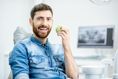 Man`s portrait in the dental office. Portrait of a handsome bearded man with healthy smile in the dental office royalty free stock photography
