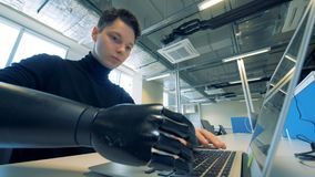Man`s prosthetic arm typing on a laptop. Robotic cyborg arm concept. Close up of young man`s prosthetic arm typing on a laptop. 4K
