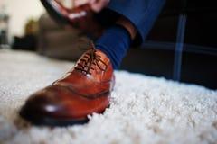 Man` s räcker band av skosnöret av hans nya bruna läderskor brudgum Royaltyfri Bild