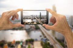 Man` s räcker den hållande smartphonen som tar fotoet av den Bangkok staden som är thailändskt Royaltyfria Bilder
