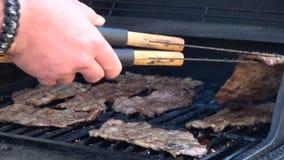 Man` s räcker matlagningkött på galler lager videofilmer