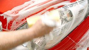 Man` s räcker washes en billykta i en röd bil arkivfilmer