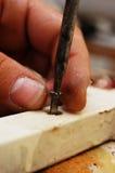 Man& x27; s ręka śrubuje śrubę w kawałek drewno Zdjęcie Royalty Free
