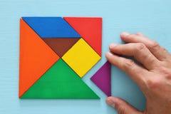 man& x27; s ręka trzyma brakującego kawałek w kwadratowej tangram łamigłówce nad drewnianym stołem, Fotografia Stock