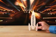 man& x27; s ręka trzyma drewnianą rakietę z słowem nad błyskotliwości czerni tłem - strategia - Zdjęcie Stock