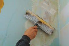 Man& x27; s ręka w szarej rękawiczce z szpachelką w remontowym pokoju obraz royalty free