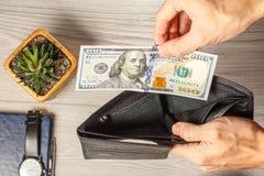 Man& x27; s ręki trzyma pustego czarnego rzemiennego portfel i 100 dolarów bi Fotografia Stock