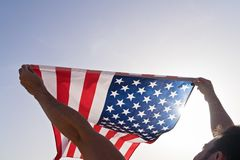 Free Man`s Raised Hands With Waving American Flag Against Clear Blue Sky Royalty Free Stock Images - 152268189