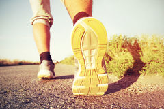 Man's running legs on the paved road Stock Photo