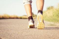 Man's running legs on the paved road Stock Photography
