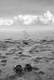 Man's sandals on sand. Traces leave to horizon Royalty Free Stock Photo