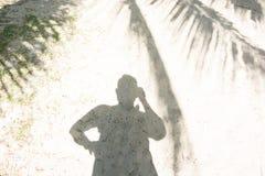 Man& x27; s schaduw in schaduw van kokosnotenpalmen bij het strand in zonnige dag Stock Fotografie