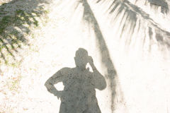 Man's shadow in shade of coconut palm trees at the beach in sunny day. Man's shadow in shade of coconut palm tree leaves on the beach at seaside in sunny day Stock Photography