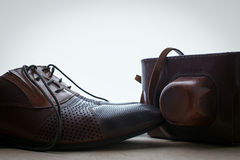 Man's shoes and a camera in a leather case Stock Photo