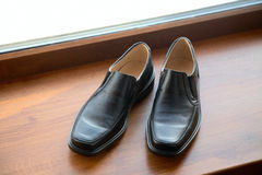 Man's shoes stand on a window sill Stock Photos
