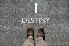 Man`s shoes view from above, word destiny and an arrow indicating the direction with copy space for your text. Man`s shoes view from above, word destiny and an royalty free stock images