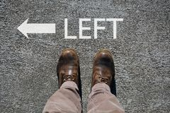 Man`s shoes view from above, word left and an arrow indicating the directions with cpy space for your text royalty free stock images