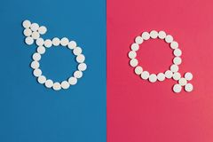 Man`s sign Mars Woman`s Venus sign made from pink and blue pills on pink background stock photography