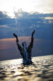 Mans silhouette with raised hands out of the sea w. Athletic mans silhouette with his hands raised in the air with splash enjoying the summer sea on a beautiful Stock Photo