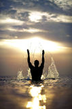 Mans silhouette with raised hands out of the sea w. Athletic mans silhouette with his hands raised in the air with splash enjoying the summer sea on a beautiful Stock Photos