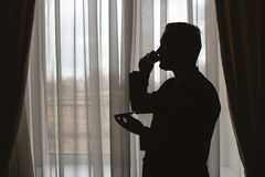 Man`s silhouette. At the window with cup in hand Stock Image