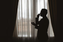 Man`s silhouette. At the window with cup in hand Stock Images