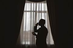 Man`s silhouette. At the window with cup in hand Royalty Free Stock Photo