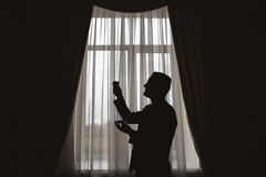 Man`s silhouette at the window with cup. In hand Royalty Free Stock Image